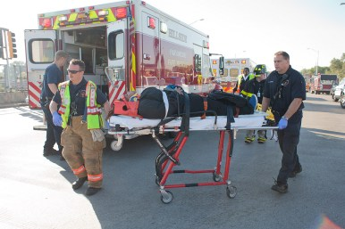 Paramedics take an injured passenger towards a waiting ambulance on Harlem Avenue in Forest Park. Thirty-three passengers were transported to area hospitals but none of the injuries were life-threatening. (David Pierini/staff photographer)