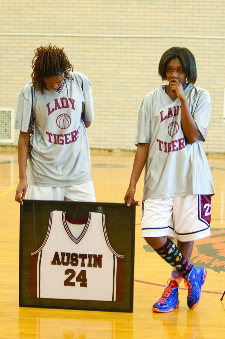 NO. 1: Amari Williams and Star Jones, members of the Austin campus girl's basketball team, hold the jersey of Ashley Hardmon, a 2012 gradutes who was shot to death in July 2013. The school retired her number during a pre-game ceremony Feb. 6. (DAVID PIERINI/Staff Photographer)