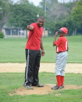 The coach Jermaine Harris shows Harris what to watch for as he pitches. The West Garfield Park Little League hosted the game against Bloomington little leaguers. Despite a national decline in inner cities, baseball has found its way into the hearts of Austinites. (Jennifer Wolfe/Contributor)