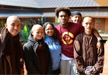 Peaceful journey: Westsiders Marquetta Monroe, 19, and Dennis Johnson 23, pose with monks and nuns at Thai Plum Village in Thailand. Monroe and Johnson traveled to Asia last December as part of the Peace Exchange program, which trains Chicago youth to combat violence issues in their home communities. (Photos courtesy Peace Exchange program)