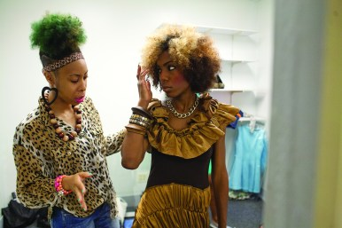 Designer Chanecia Williams talks to model Tyesha Smith about how Smith will walk down the runway in her dress. (David Pierini/Staff Photographer)