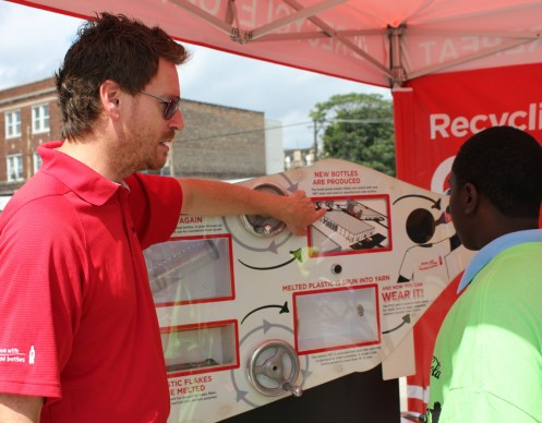 A representative from Coca Cola teaches one of the youth attendees about the recycling process during the fitness fun fest. The Coca Cola Company was also among the key corporate sponsors of this year's event.