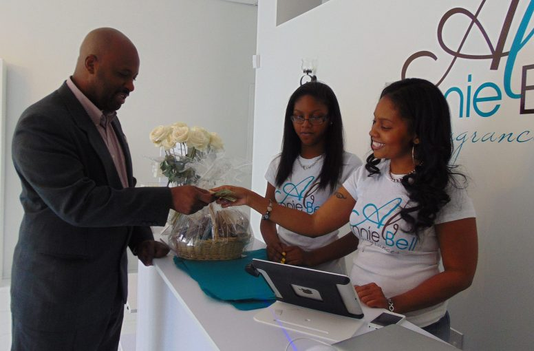 Malcolm Crawford, executive director of Austin African American Business Networking Association, buys a gift basket from Annie Bell Fragrances owner Fallon Johnson during his organization's Oct. 4, shopping event for the new Austin business. PHOTOS BY TERRY DEAN