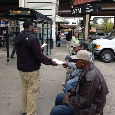 Tevin Smith passes out flyers to men at Lake and Laramie. (Michael Romain/Contributor)
