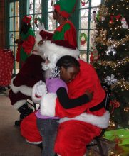 Jaquir Anderson, 5, got her hug in with Santa at Saturday's annual toy giveaway sponsored by Loretto Hospital.