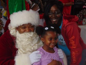 Tansha Davis and her daughter Anaila, 4, pose with Santa.