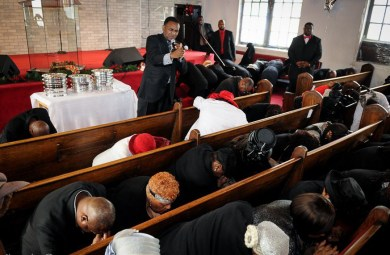 On bended knees with heads bowed, the Greater St. John Bible Church congregation prayed for the families of police shooting victims Michael Brown and Eric Garner following their Dec. 7, Sunday morning service; (Dwayne Truss/Contribution)