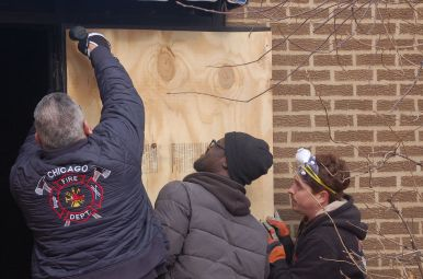 Volunteers work on the outside of Rep. LaShawn Ford's old real estate office, which he donated to a nonprofit to transform into a community center. (Michael Romain/Editor).