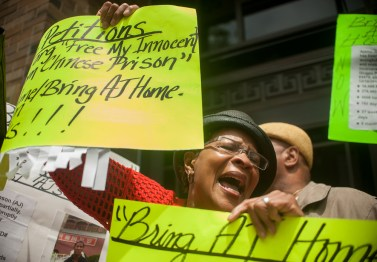 "DOWN AND OUT IN CHINA: Delial Johnson, the mother of Ajamu ""AJ"" Johnson, protests with family and friends in front of the Chinese Consulate, 100 W. Erie St., on June 19. Ajamu's family say he's being wrongly detained in a Chinese prison. 