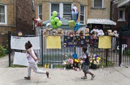 Neighborhood children walk past a memorial that blossomed in the wake of 7-year-old Amari Brown's murder on July 4. William Camargo/Staff.