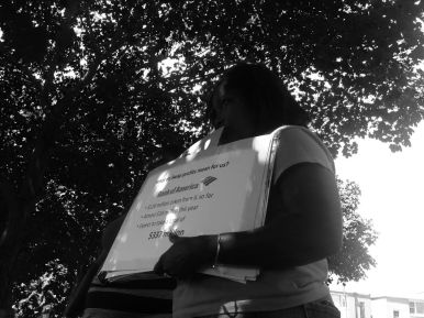 A girl holding a sign at a community teach-in hosted by the Grassroots Collaborative Thur. July 30 at LaFollette Park. Michael Romain/Staff.