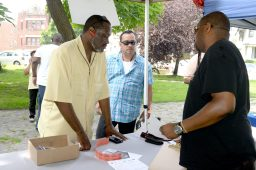 Kendall Reid of Kingdom Community sharing info about the neighborhood bus tour with Ken Atwood