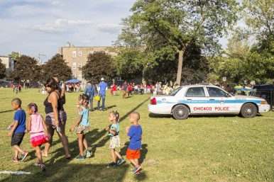 National Night Out: A family walks by a police squad car parked at Moore Park, 5085 W. Adams St., on Tue. August 4. A crowd of hundreds converged on the park for National Night Out, an event sponsored by police departments across the U.S. and Canada to strengthen relationships between cops and residents. | Alex Wroblewski/Contributor