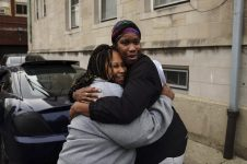 Erica Shelton, left, embraces Tiffany Davis, 43, during an Oct. 23 demonstration in the parking lot of St. Angela School in Austin. | William Camargo/Staff.