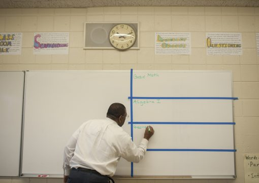 Emmanuel Littrell, a math teacher at Camelot Academy, writes on a white board in preparation for a class during the West Garfield Park school's open house and grand opening on Oct. 28, 2015. | William Camargo/Staff.