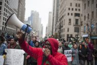 Chicago Teachers Union organizer Brandon Johnson yells through a bullhorn during the Nov. 27 Laquan McDonald Black Friday protest on the Magnificent Mile. The march, which drew at least 2,500 people, was led by Rev. Jesse Jackson and other activists, elected officials and community leaders. On Nov. 24, police released video showing McDonald getting shot 16 times by Chicago police officer Jason Van Dyke last October. | William Camargo/Staff.