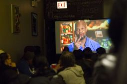 """A crowd watches local businessman and restaurant owner Quentin Love compete on an episode of """"Guy's Grocery Games"""" during a Dec. 15 watch party at Love's Turkey Chop Gourmet Grill, the West Side restaurant he owns. Love, who won the competition, donated his proceeds to the soup kitchen the restaurant operates. 