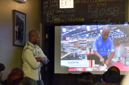 """A crowd watches local businessman and restaurant owner Quentin Love, standing, compete on an episode of """"Guy's Grocery Games"""" during a Dec. 15 watch party at Love's Turkey Chop Gourmet Grill, the West Side restaurant he owns. Love, who won the competition, donated his proceeds to the soup kitchen the restaurant operates. 