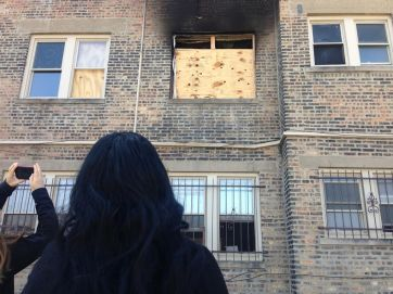 Gayina Washington looks up at a second floor apartment unit at 312 N. Central Ave., which caught fire on April 2. She claims the building's owners increased her rent late last year without fixing numerous code violations. | Michael Romain/Staff