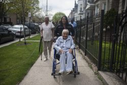 Alma Richmond, 100, is rolled down the 3900 block of Monroe Street, now Honorary Alma Richmond Way, by a relative and accompanied by one of her best friends, beautician Gertrude Hudson, left, during an April 21 sign-unveiling. Richmond has been living on her block for nearly 60 years. | William Camargo/Staff