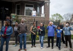 Neighbors, friends and relatives of Alma Richmond photograph a street sign marking part of West Monroe Street Alma Richmond Way during an April 21 gathering. | William Camargo/Staff