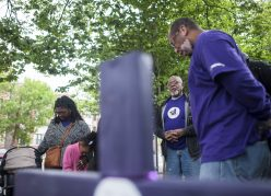 Rev. Gerald Smith, right, prays during a May 20 gathering at the site of the first purple cross his church planted at the corner of Central Ave. and Jackson Blvd. The crosses are meant to bring attention to gun-related injuries or deaths. | William Camargo/Staff