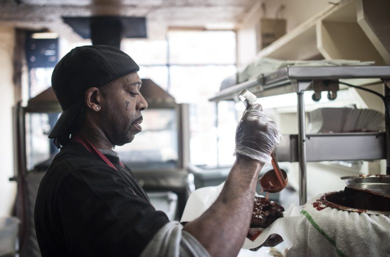 Eddie Harris, 50, prepares a meal inside Ben's BBQ in Austin on May 20. Harris, who has served 27 years in prison, is one of the many ex-offenders Ben's co-owners, Linda Leslie and Tyrone Wideman, have employed since opening the restaurant 12 years ago. | William Camargo/Staff