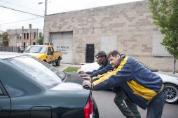 Two men push a stalled vehicle in the West Garfield Park neighborhood to auto body mechanic Glen Gray, a Jamaican immigrant who is among many community residents who expressed shock and disappointment at the election of Donald J. Trump to the presidency. | William Camargo/Staff