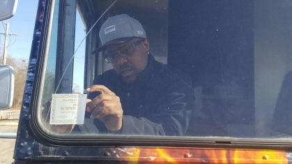 Chris Jossell sticks his food truck license to the window of CJ's BBQ Cruiser. | Submitted photo