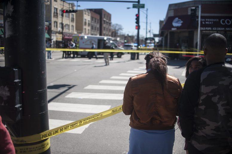Bystanders gather near the scene of a murder in Austin on April 7. One man was killed and several bystanders were wounded when the occupants of a gray or white vehicle drove by Corcoran Grocery and began shooting in the middle of the day. | William Camargo/Staff