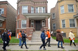 Volunteers and participants walk down the road going door-to-door with information on the spike in recent carjackings in the area on Friday, Nov. 17, during a Good Neighbor Campaign rally on Massasoit Avenue near Augusta Street in Chicago's Austin neighborhood. | ALEXA ROGALS/Staff Photographer