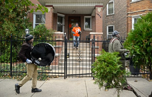Volunteers leave information in mailboxes as members of the Exodus walk down the streets performing on Friday, Nov. 17, during a Good Neighbor Campaign rally on Massasoit Avenue near Augusta Street in Chicago's Austin neighborhood. | ALEXA ROGALS/Staff Photographer