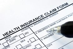 File the health insurance claim form with a pen