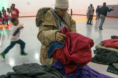 Janis Harris, who has family members in Austin, grabs a red coat during Stop The Violence's Unity in the Community Coat Drive. Like many residents, Harris saw the coat drive while walking by and decided to partake in the event. | SEBASTIAN HIDALGO/Contributor