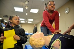 Sisters Cheyenne Anderson, 9, left, and Maya Anderson, 7, above, both of Chicago, learn how to correctly perform cardiopulmonary resuscitation (C.P.R.). | ALEXA ROGALS/Staff Photographer