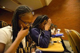 While students from Ella Flagg Young Elementary School, bow their heads for a prayer from Rev. Stanley Stephens. | ALEXA ROGALS/Staff Photographer