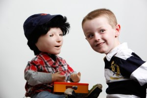 Dr Ben Robins of the University of Hertfordshire with Kaspar the social robot and a young child with autism.