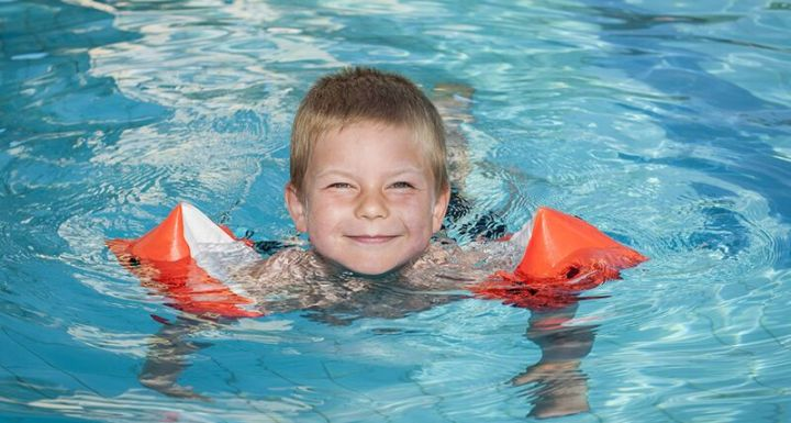 young boy in pool with floaties
