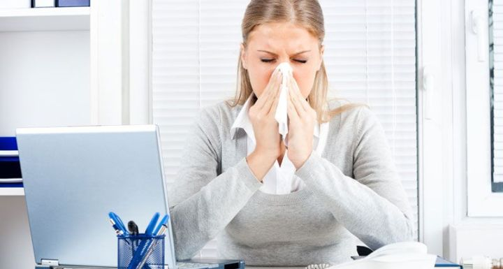 woman blowing her nose at her desk