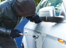 Ein Autodieb bricht einen PKW auf. © sdecoret. Fotolia.com