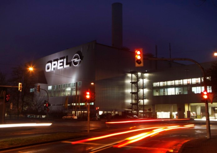 Vehicles drive past the Opel plant in Bochum