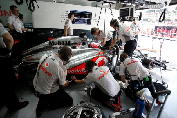 The team work on the MP4-28 of Jenson Button in the garage
