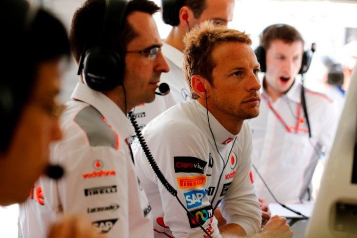 Jenson Button looks at data with engineers
