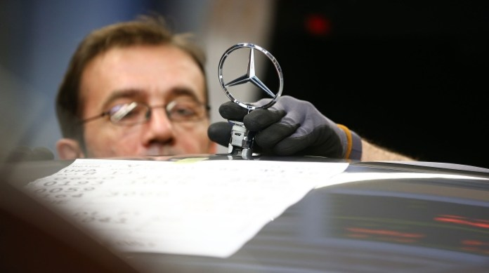 SINDELFINGEN, GERMANY - JANUARY 24: An employee mounts a Daimler AG Mercedes-Benz emblem to the hood of a S-Class sedans on the assembly line at the Mercedes-Benz plant of Daimler AG on January 24, 2014 in Sindelfingen, Germany. Daimler is scheduled to announce financial results for 2013 on February 6. (Photo by Thomas Niedermueller/Getty Images)