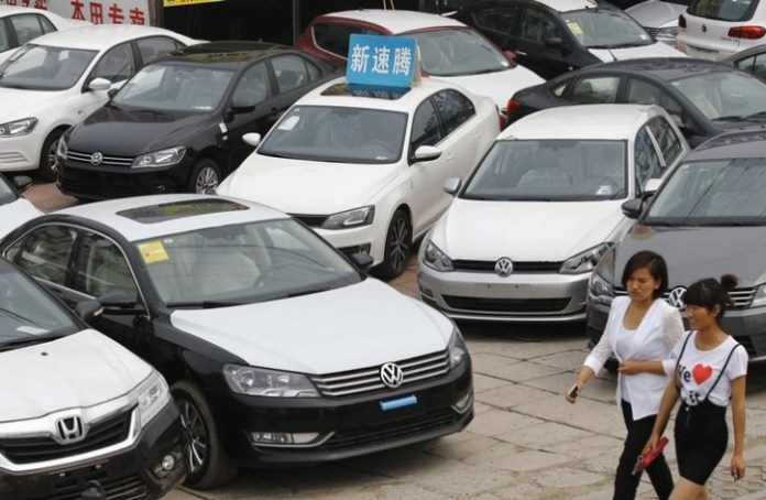 Women walk past Volkswagen and Honda cars on display at an automobile market in Beijing