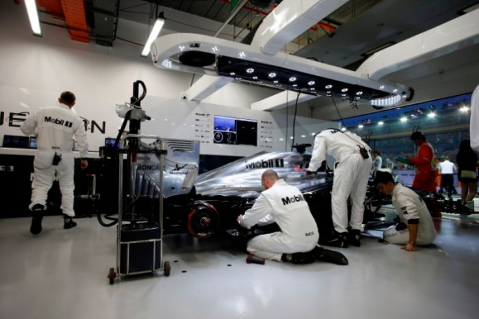 Mechanics work on Jenson Button's car.