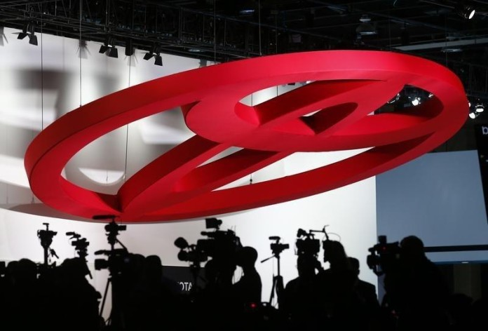 Members of the media are shown under a large Toyota logo during the first press preview day of the North American International Auto Show in Detroit