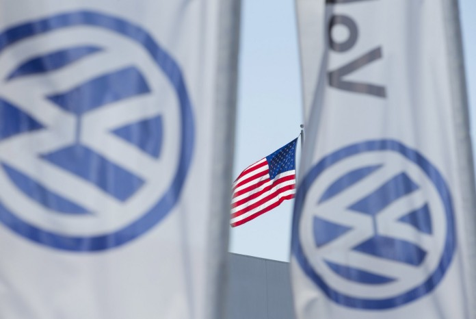 An American flag flies next to a Volkswagen car dealership in San Diego, California September 23, 2015. Volkswagen Chief Executive Martin Winterkorn resigned on Wednesday, succumbing to pressure for change at the German carmaker, which is reeling from the admission that it deceived U.S. regulators about how much its diesel cars pollute. REUTERS/Mike Blake
