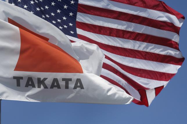 A flag with the Takata logo flies alongside an American flag outside the Takata Corporation in Auburn Hills