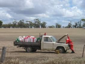 Papai Noel parado a frente de seu caminhão antigo com o capô aberto e com presentes na carroceria.